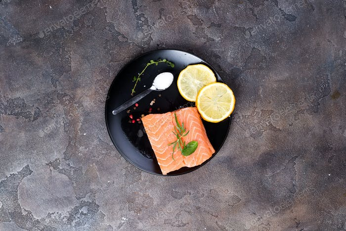 Filetes de salmón en Hielo con limón y sal en plato negro. Proteínas magras.