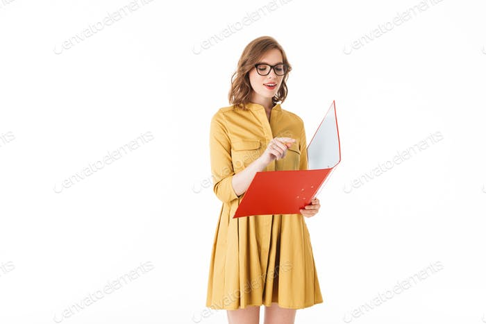 Pretty thoughtful lady in eyeglasses and yellow dress standing with red folder in hand