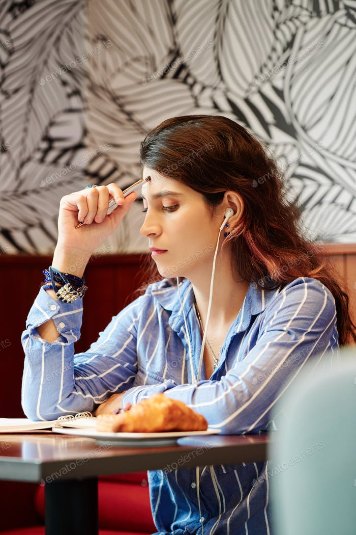 Pensive female student in cafe