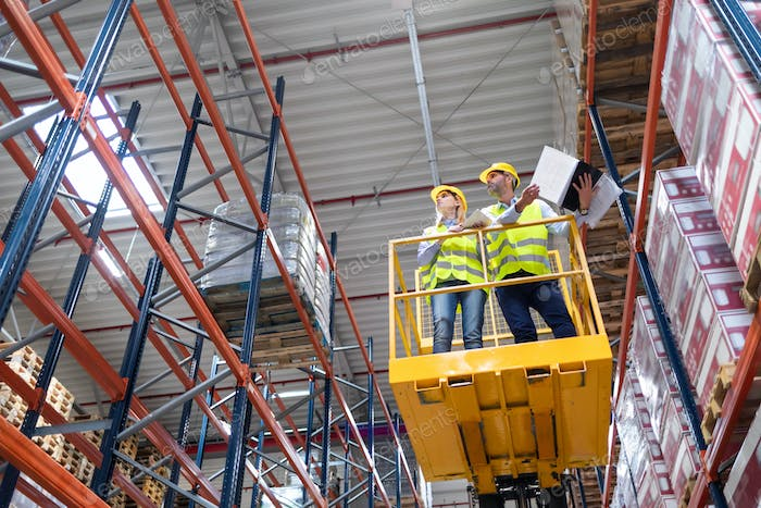 Warehouse workers on the height using lift work platform to check inventory