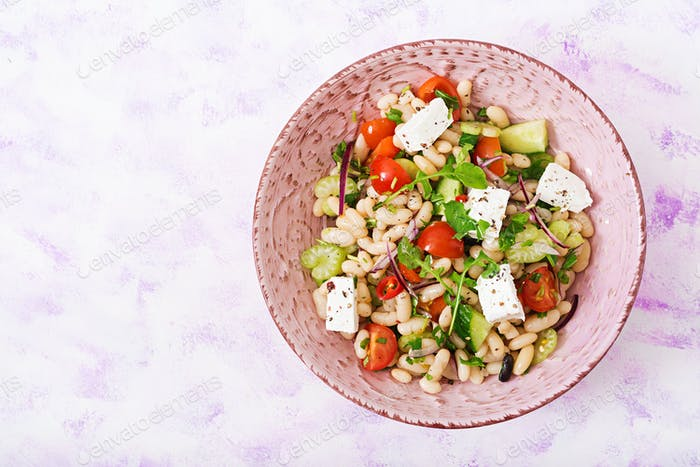 Salad of white beans, tomato, celery, cucumber, arugula, red onion and feta cheese in bowl.