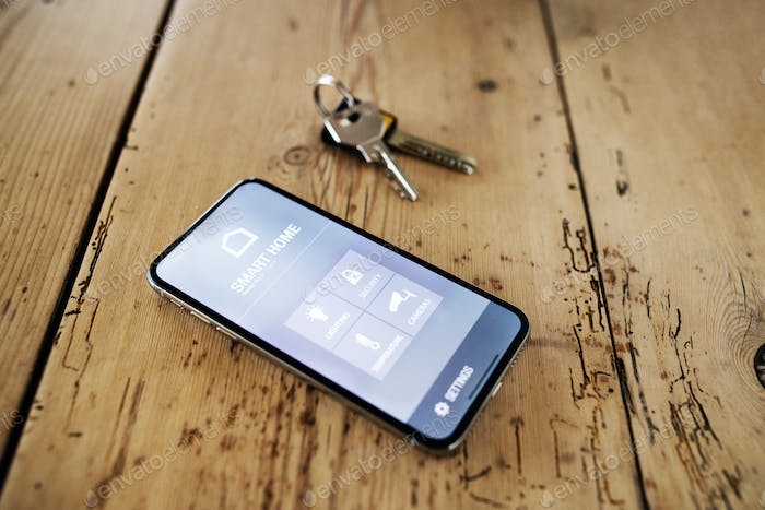 A smartphone with smart home screen and keys on wooden table.