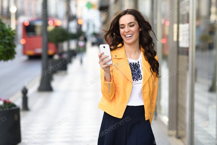 Young brunette woman smiling and looking at her smartphone