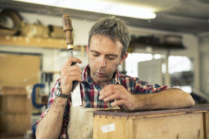 Un restaurador de muebles antiguos que sostiene un cincel y trabaja en una pieza de mobiliario.