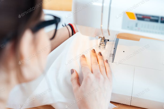 Woman seamstress working and sewing in studio