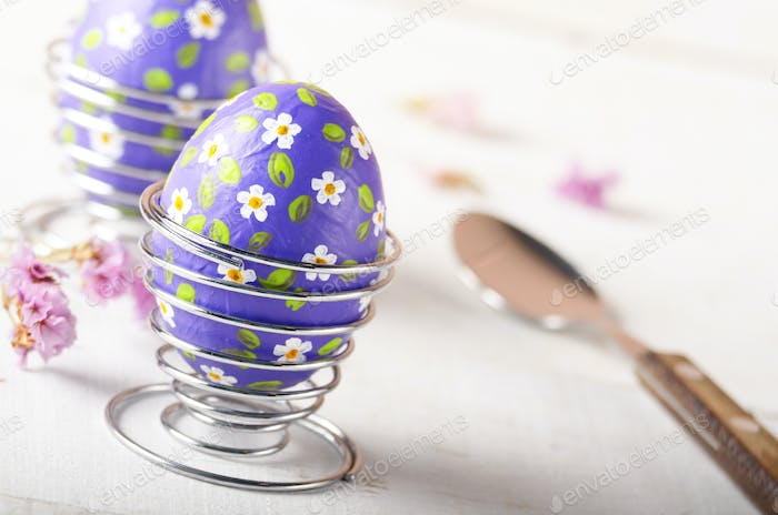 Wire egg cups with painted easter eggs on white table