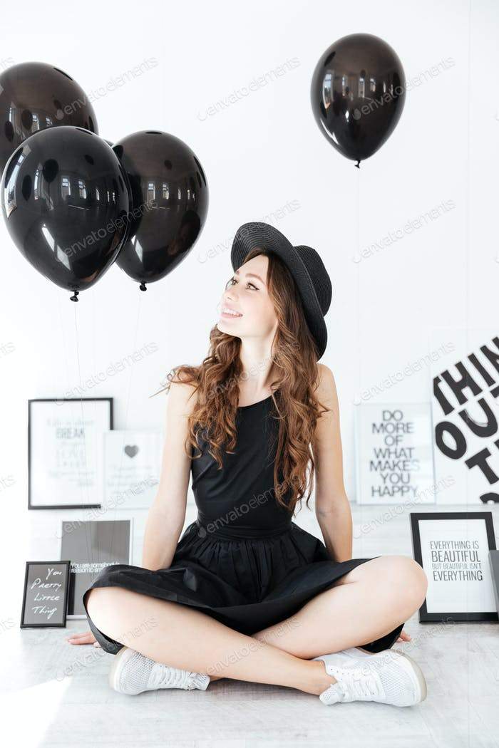 Happy charming young woman with black balloons and posters sitting