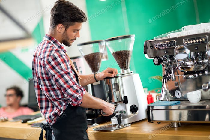 Satisfied barista steaming milk