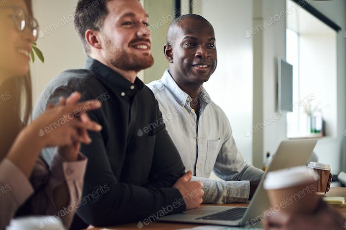 Diverse businesspeople smiling while sitting together in a boardroom