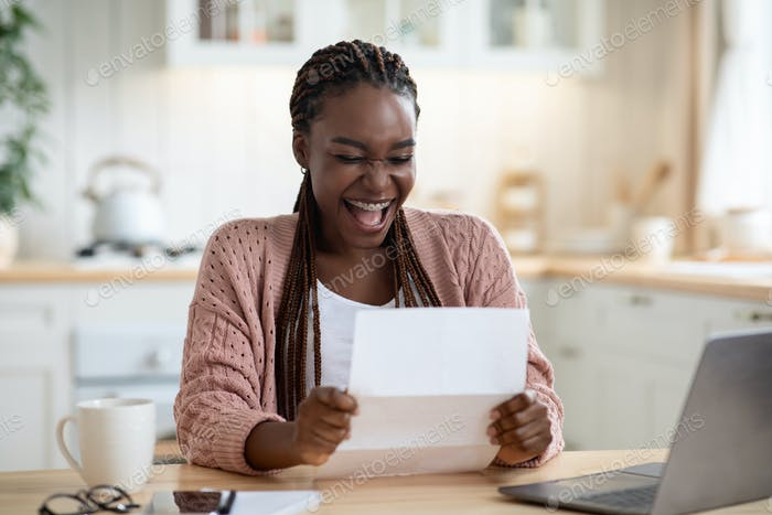 Overjoyed Black Woman Reading Letter In Kitchen And Exclaiming With Excitement