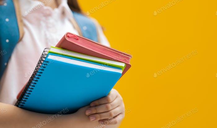 Kind mit Büchern auf dem Hintergrund der gelben Wand.