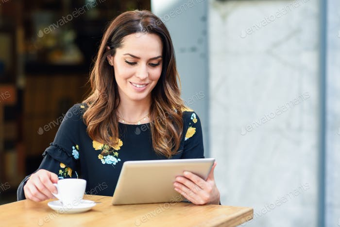 Middle-aged woman using tablet on coffee break in urban cafe bar