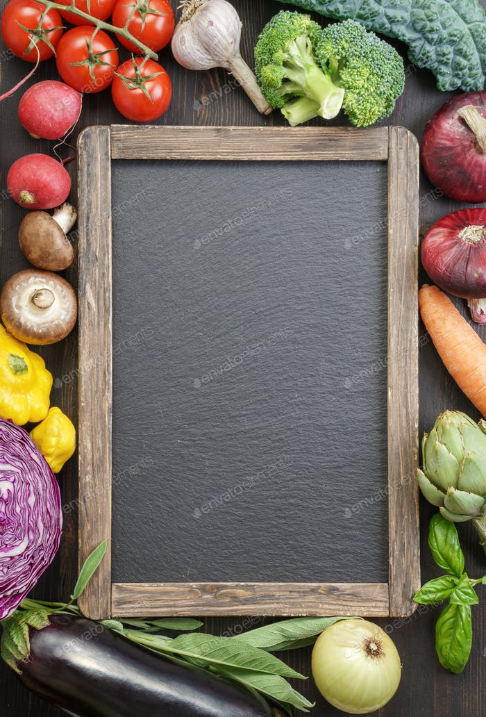 Slate board among various fresh vegetables