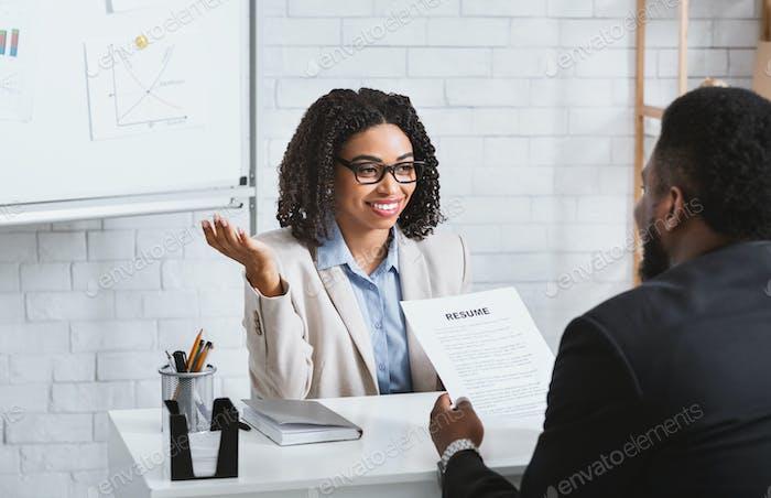 Freundlicher Personalmanager interviewt schwarzen Kandidaten während Vorstellungsgespräch im modernen Büro