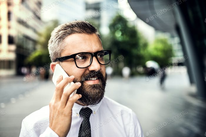 A close-up of hipster businessman with smartphone in the city, making a phone call.