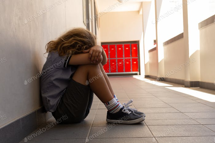 Sad schoolgirl sitting on the floor with his head down in the school corridor