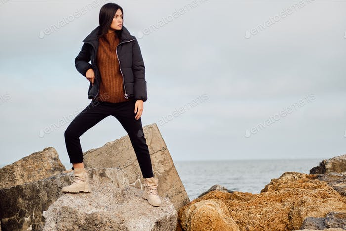 Attractive Asian girl in down jacket thoughtfully looking posing away on big stones by the sea