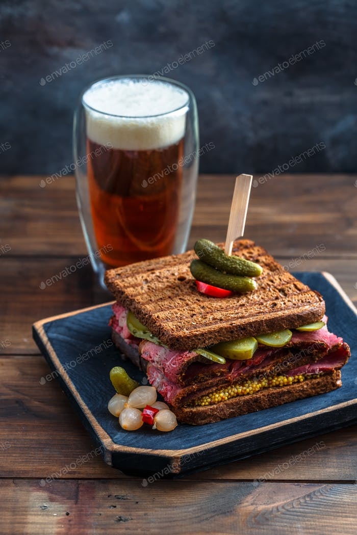 Delicious huge pastrami sandwich with beer and pickle