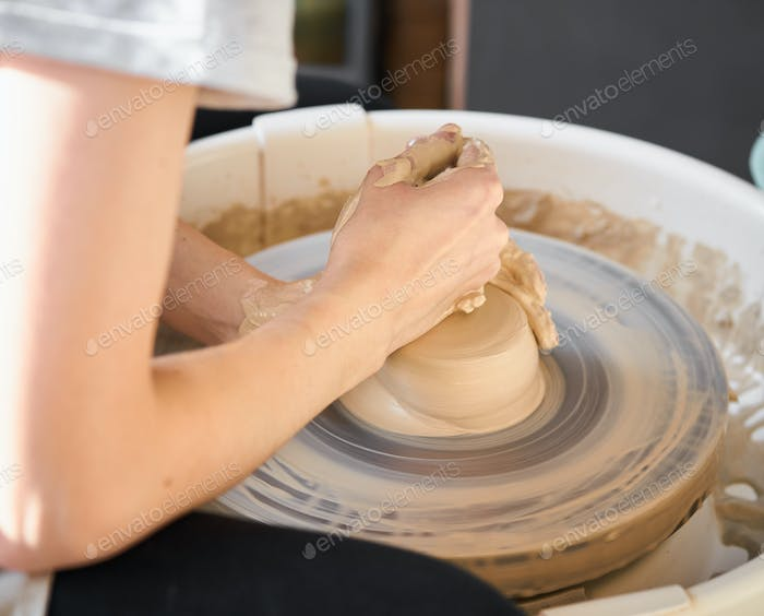 Woman making ceramic pottery on wheel, hands close-up, creation of ceramic ware