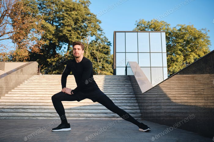 Young attractive sporty man stretching during morning workout in city park