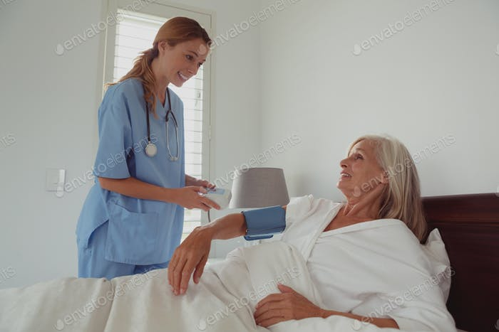 Caucasian female doctor checking blood pressure of active senior woman in bed in bedroom at home