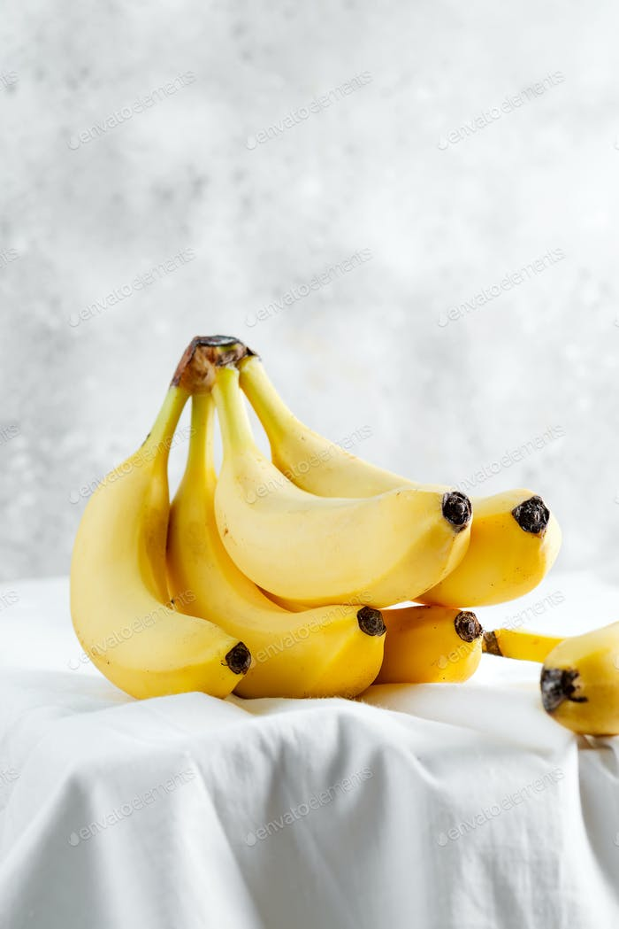 Branch of freshly picked natural organic banana fruits on a white tablecloth against light grey wall