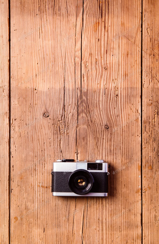 Vintage camera laid on table. Wooden background. Studio shot