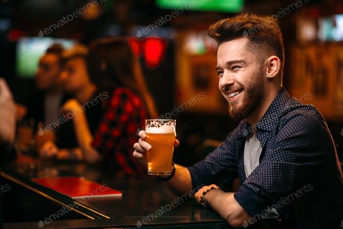 Mann trinkt Bier an der Bartheke in einem Sport-Pub