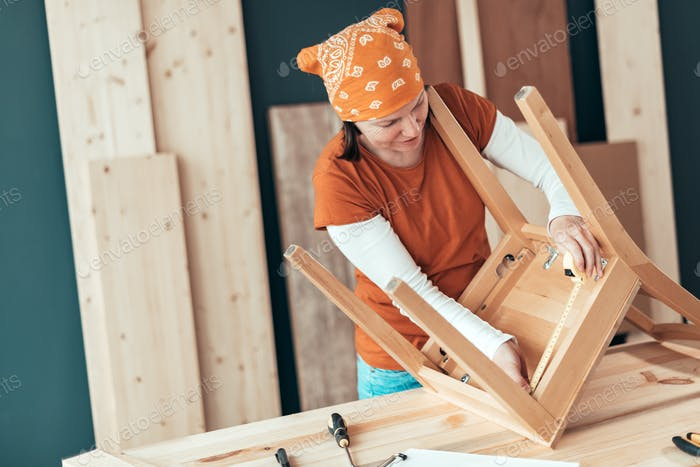 Female carpenter repairing wooden chair seat in workshop