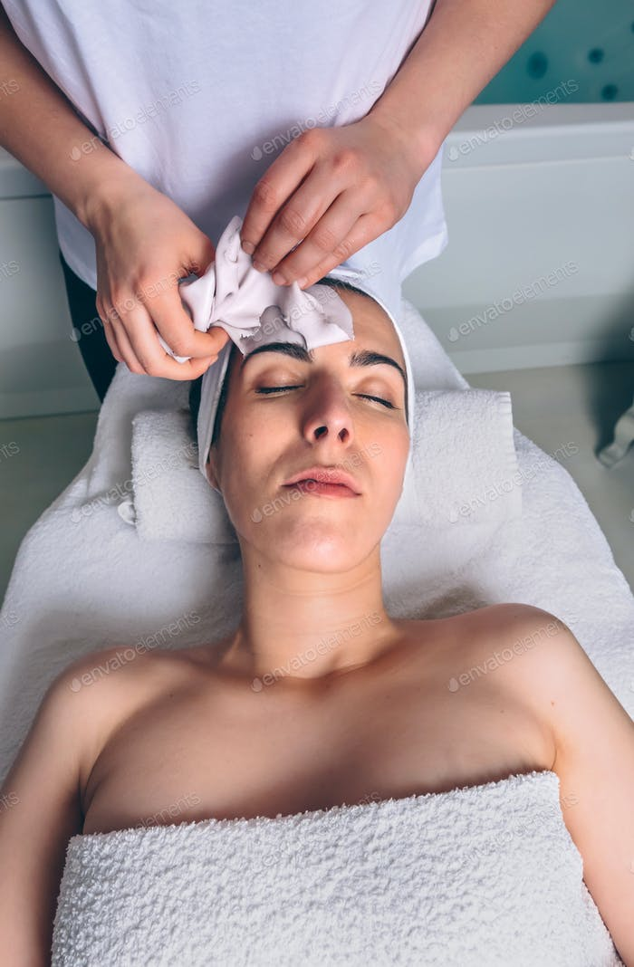 Beautician removing facial mask to woman in spa