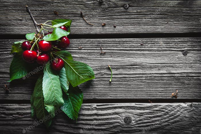 Wooden background with several delicious cherries on green leaves