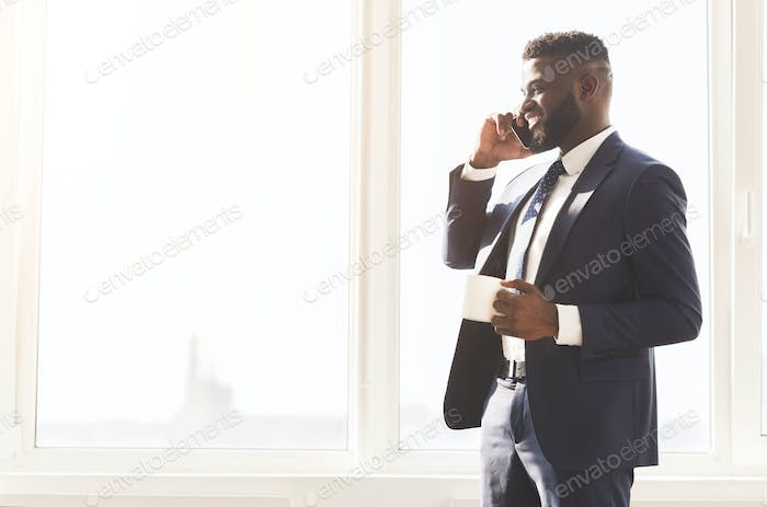 Attractive businessman talking by phone and drinking coffee near window
