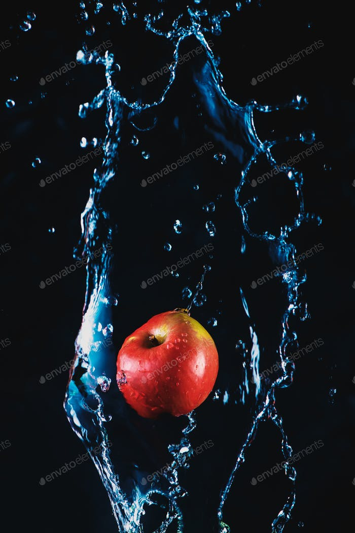 Apple in a splash of water on a dark background. High-speed motion food photography with copy space