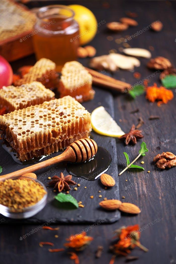 Zutaten für gesundes heißes Getränk. Zitrone, Ingwer, Minze, Honig, Apfel und Gewürze auf dunklem Hintergrund