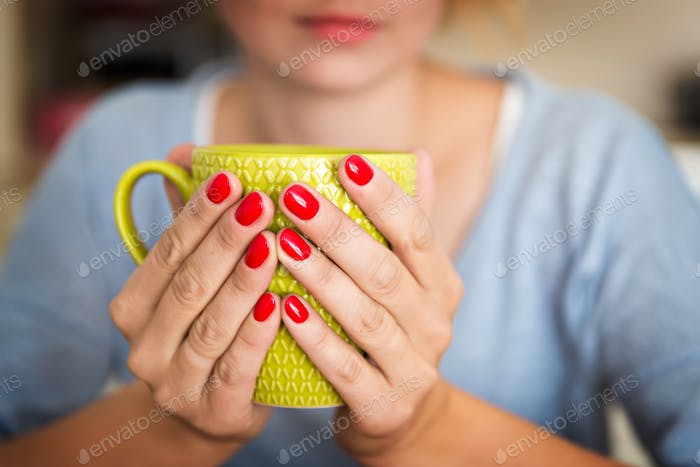Hands holding a green mug