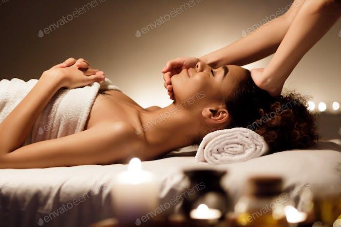 Spa treatment. Afro woman enjoying face massage