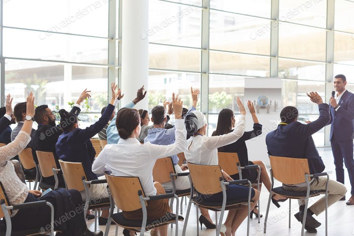 Business people raising hands at conference