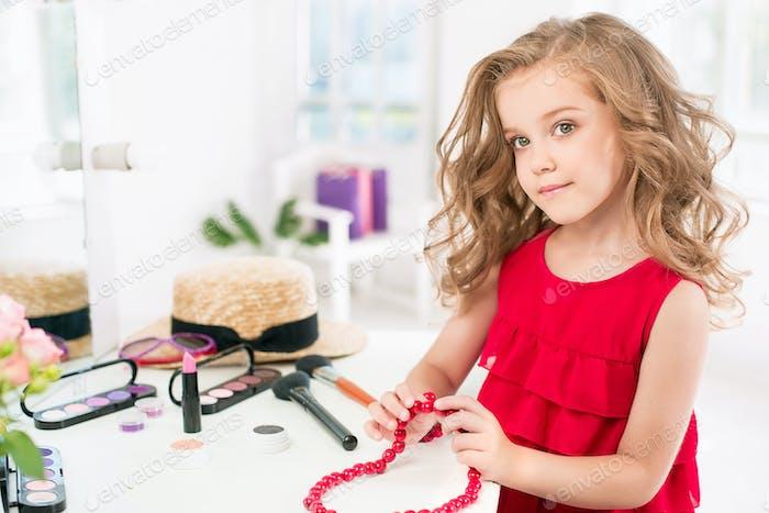 Ein kleines Mädchen mit Kosmetika. Sie sitzt im Schlafzimmer der Mutter und sitzt in der Nähe des Spiegels.