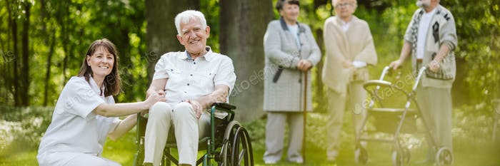 Mature caregiver and elder man on the wheelchair