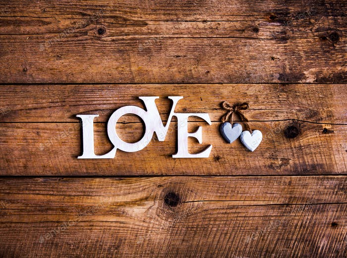 Wooden letters forming word LOVE written on wooden background. St. Valentine's Day. two hearts