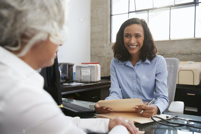 Junge weibliche Analytikerin in Absprache mit Seniorin