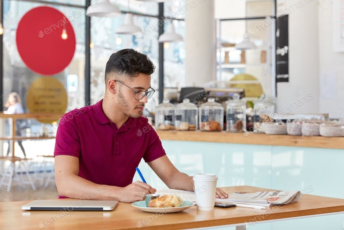 Photo of stylish man with trendy haircut, writes records in notepad, focused in newspaper, drinks ta
