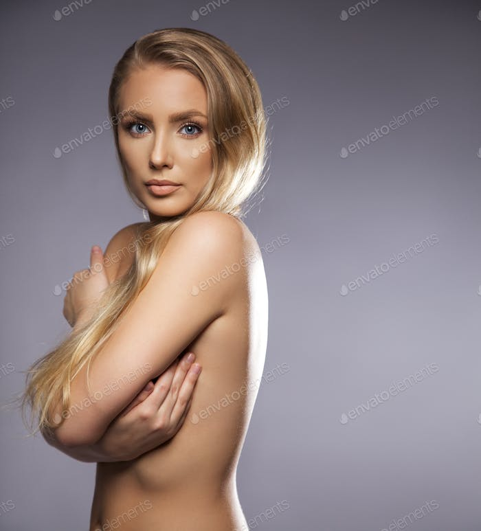 Naked young female covering her breast with hands