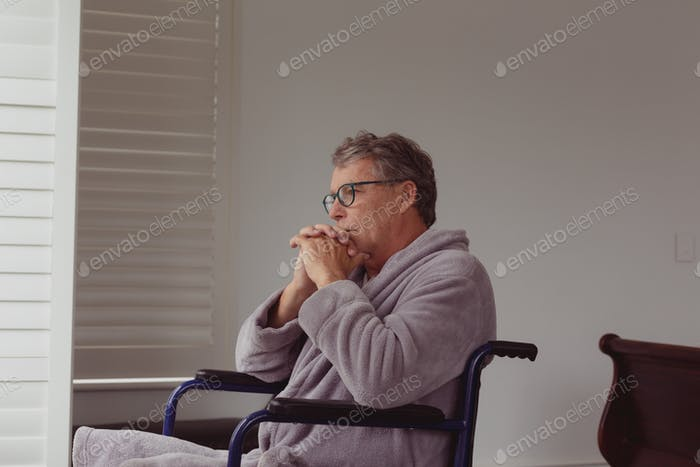 Thoughtful disabled active senior Caucasian man looking through window on wheelchair
