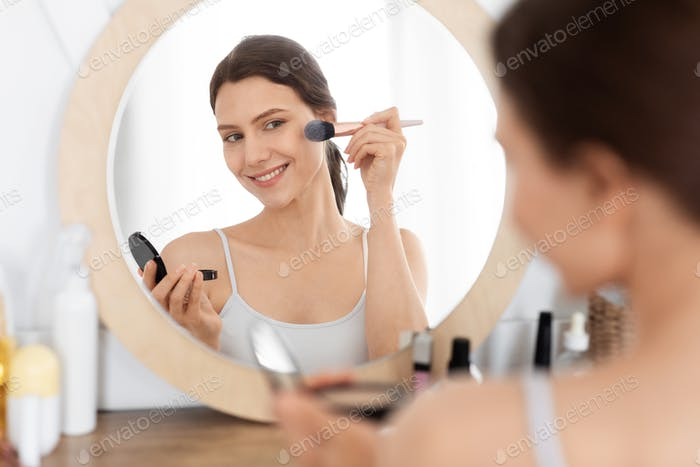 Happy pretty woman applying blush on her face