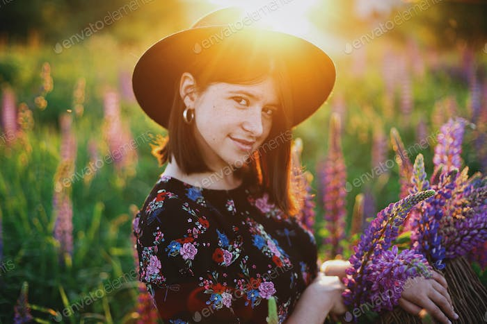 Portrait of woman in lupine field in countryside meadow at sunset. Tranquil atmospheric moment