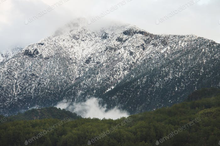 Green slopes of the Taurus mountains covered with snow