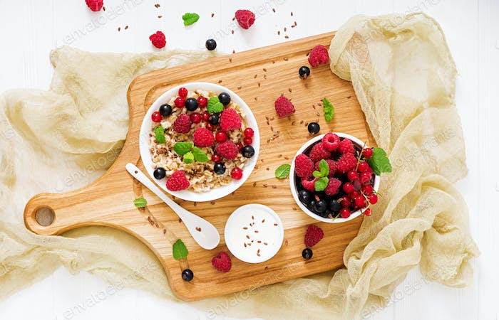 Tasty and healthy oatmeal porridge with berry, flax seeds and yogurt