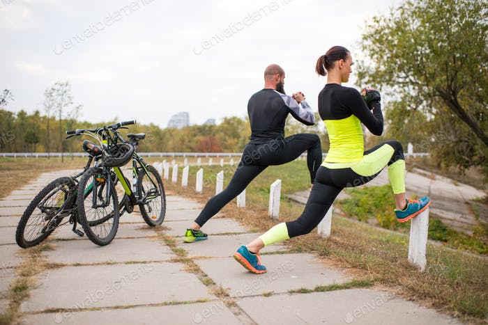 Couple of cyclists limbering-up before ride in park