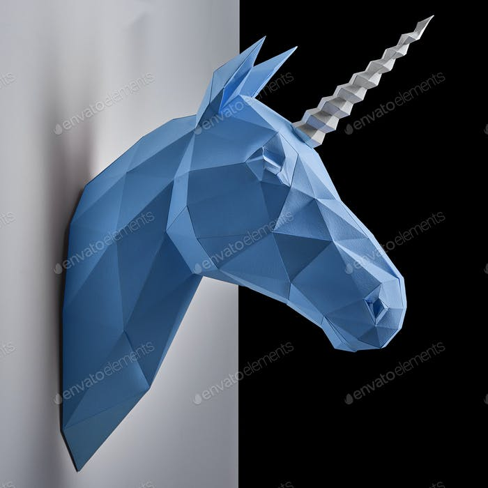 Blue unicorn's head hanging on the contrast white and black wall